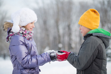 A smiling boy with a girl in a hat and scarf in winter park