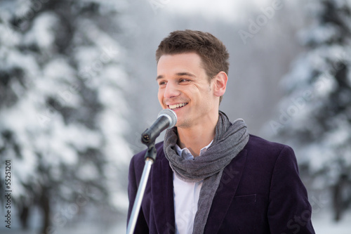 singer in suit and scarf stands outdoors in winter