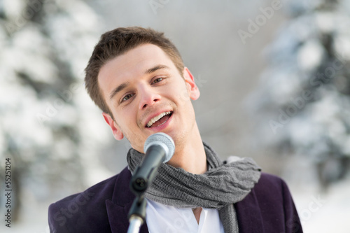 The singer in suit and scarf sing outdoors in winter