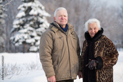 Portrait of an elderly couple in park in winter, focus on a man.