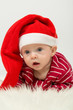 Baby boy with big eyes, with mouth open in Santa Claus cap