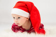 Baby boy with big eyes in Santa Claus cap