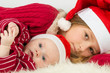 Little girl with baby boy lie in hats of Santa Claus