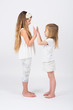 Two girls dressed in white playing slapping each others hands
