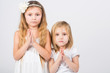 Two girls dressed in white palms folded in prayer