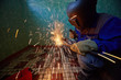 Welder in protective suit and mask welds metal pipes