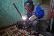 Welder in protective suit and mask welds metal pipes squtting
