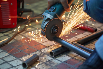 Male hand cuts off pieces of water pipe with angle grinder