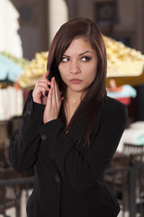 Young woman in a business attire places her hand over her phone