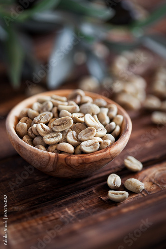 Green coffee beans in wooden bowl, selective focus
