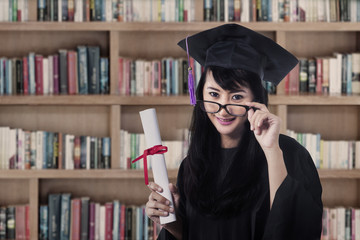 Asian female graduate smiling at library