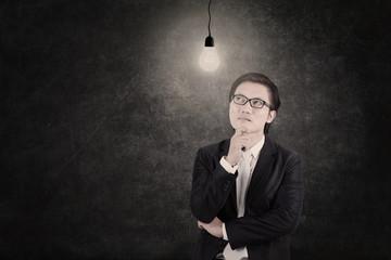 Businessman under lit bulb thinking of idea