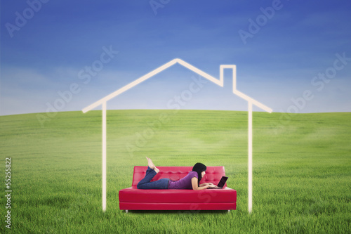 Asian female lying on sofa in dream house outdoor