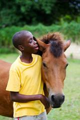 boy giving horse a hug