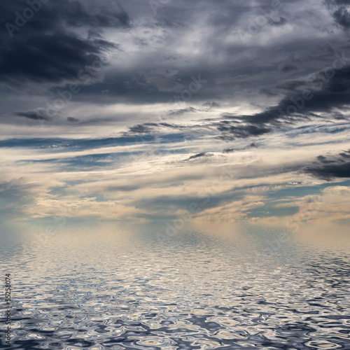 Sky with dark clouds reflected in water surface.
