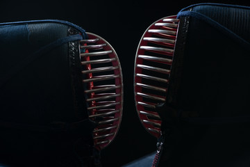 Two kendo helmets facing each other over dark background