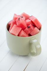 Cubes of watermelon in a cup, vertical shot