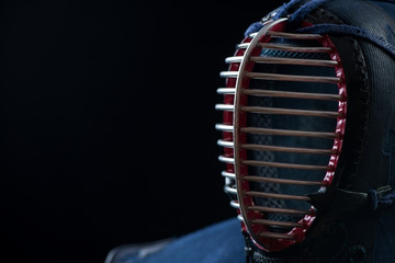 Kendo helmet over dark background, horizontal shot, copyspace