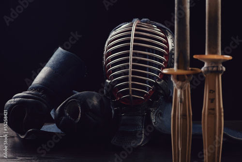 Kendo equipment over dark background: men, kote and shinai