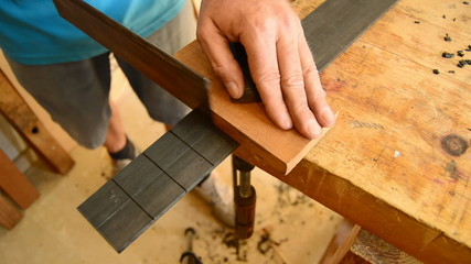 Luthier making the frets of a guitar with a hacksaw