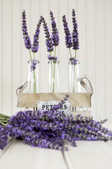 Three small vases with lavender on a white table
