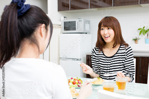 beautiful asian women eating in the kitchen