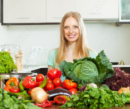 positive woman with pile of raw vegetables