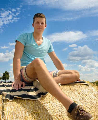Die Natur genießen: Junger Mann auf Strohballen