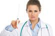 Portrait of serious doctor woman holding syringe