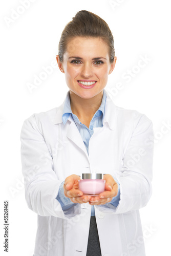 Smiling cosmetologist doctor woman showing bottle of creme