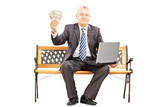 Happy mature businessman sitting on a bench and holding money