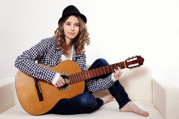 Young woman playing the guitar and sitting on a sofa