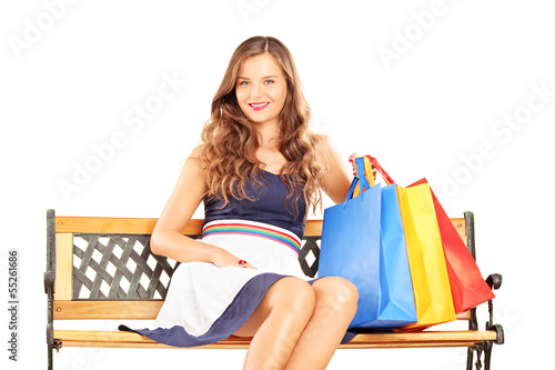 Beautiful smiling woman sitting on a bench with shopping bags