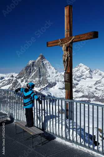 A boy in front of a cross on top of mountains
