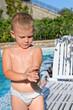 Careful little boy applying sunscreen