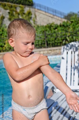 Young boy at the pool applying sunscreen