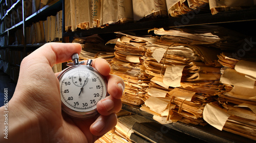 Hand with stopwatch, paper documents stacked in archive - 55266681