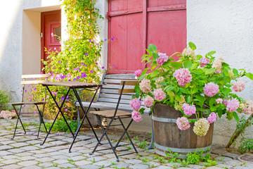 Romantischer Hauseingang mit Gartenmöbel und Pflanzen