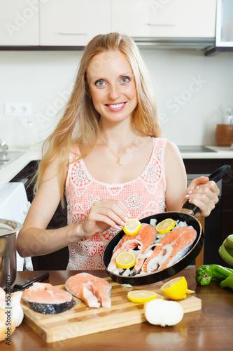 woman cooking salmon  with lemon