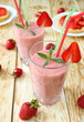 strawberry milk shake in a glass with a straw