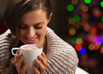 Woman with cup of chocolate with marshmallow near christmas tree