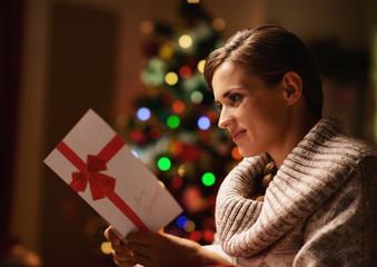 Happy young woman reading postcard in front of christmas tree