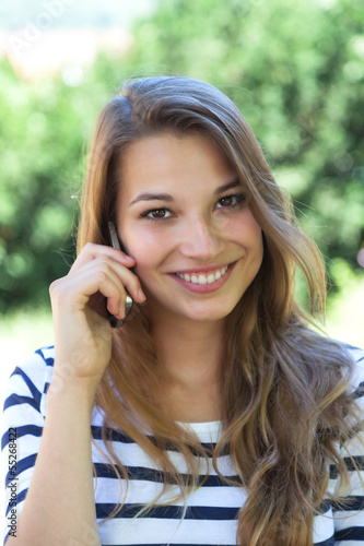 Beautiful young woman smiling on the phone in a park