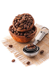 Coffee beans in ceramic bowls and measuring spoons