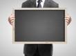businessman holding blackboard