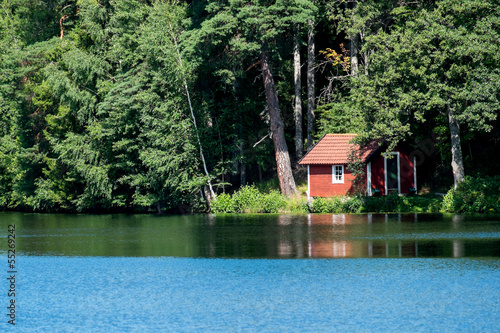 Summer in Sweden - a typical red little cottage by a lake