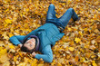 Young man laying in foliage.
