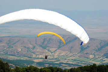 Couple paragliders on the sky