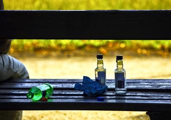 Urban alcoholism - empty bottles of vodka standing on bench