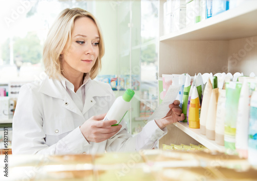 Happy pharmacist woman in pharmacy shop